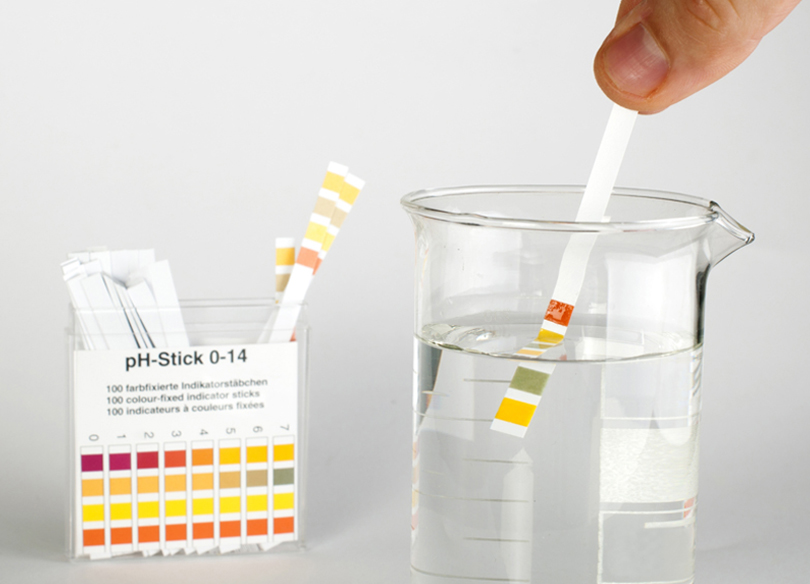 17267688 - litmus strips for measurement of acidity.beaker with water